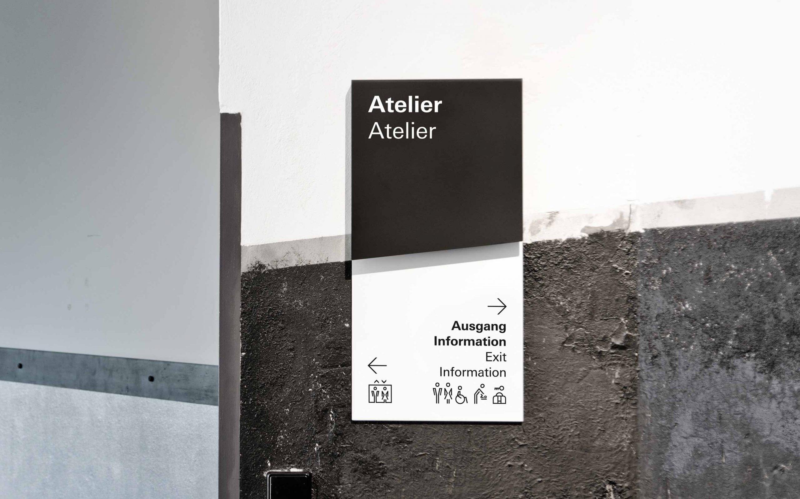Leitsystem des Museums in der Kulturbrauerei, zweiteiliges Schild, mit oberer schwarzer Primärinformation und unterer Sekundärinformation auf weiß, direkt aufgebracht auf eine der historischen Bestandswände (Denkmalschutz). Wegweiser / Zielbestätigung, Farbe: RAL 9005 und weiß. Elemente: Schrift (Univers Regular und Univers Bold), Pfeile, Icons
