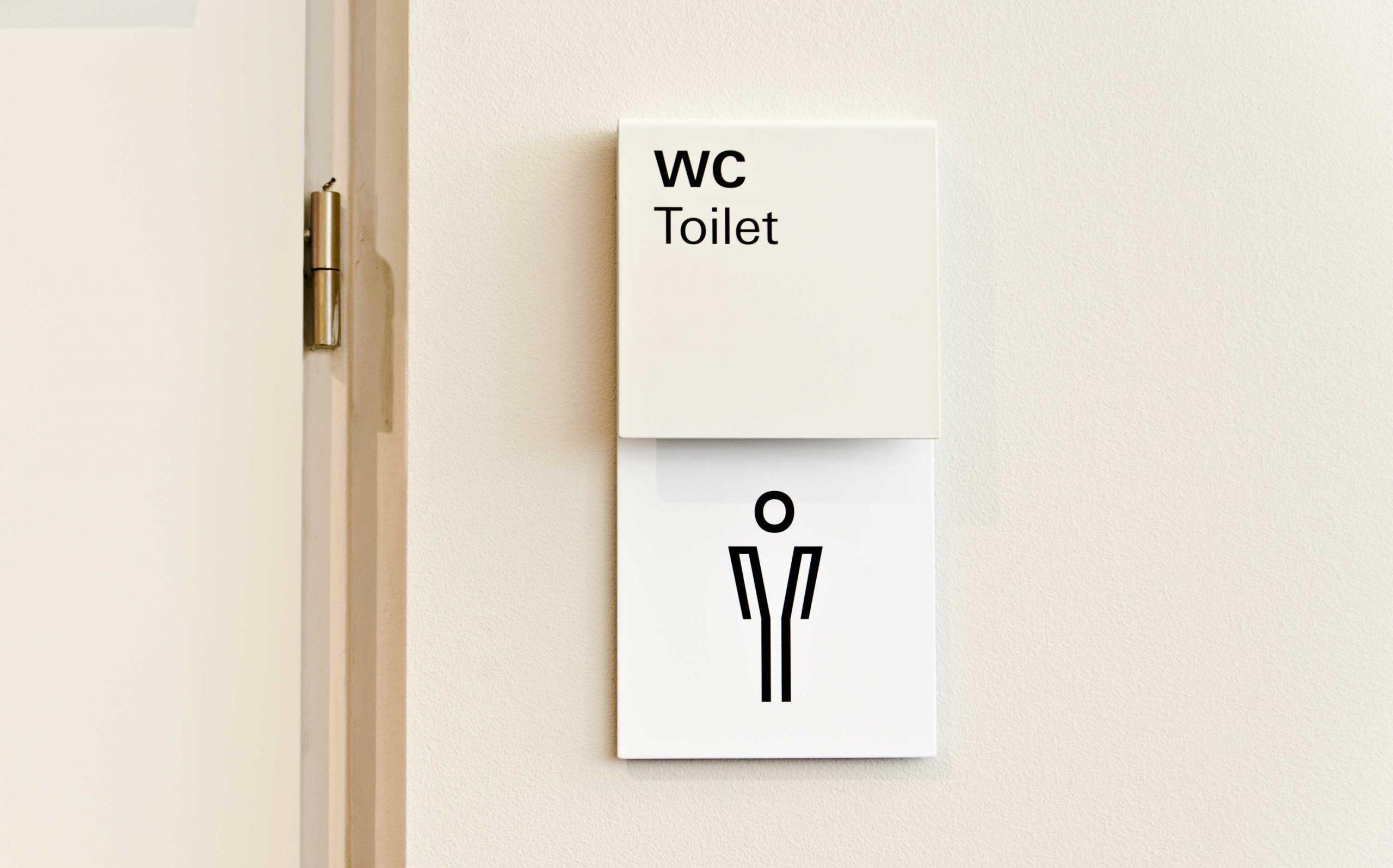 Leitsystem Museum in der Kulturbrauerei. Zielbestätigung mit Piktogramm / Icon für WC, beige-weiß. Direkt-Montage auf Vorbauwände. Farbe: RAL 1013 & weiß. Elemente: Schrift (Univers Regular und Univers Bold), Icons