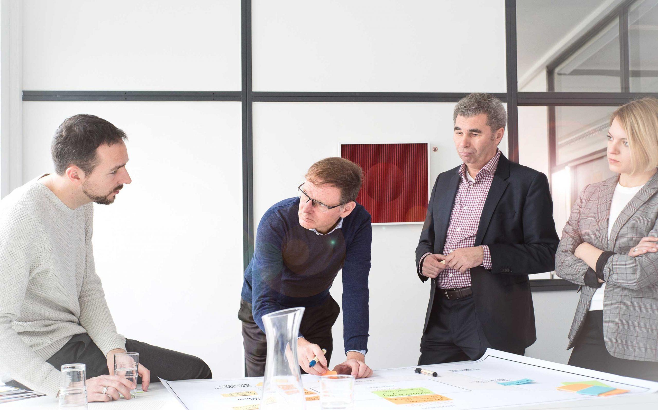 Cross Industry Consulting | Fotoshooting, mehrere Menschen stehen bei einer Besprechnung über einen Tisch gebeugt zusammen | Keywords: Corporate Design, Logo, Grafikdesign, Design, Typografie, Whitepaper, Strategie, Beratung